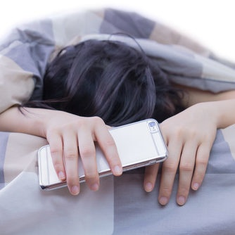 Woman sleeping and holding a mobile phone in the bed